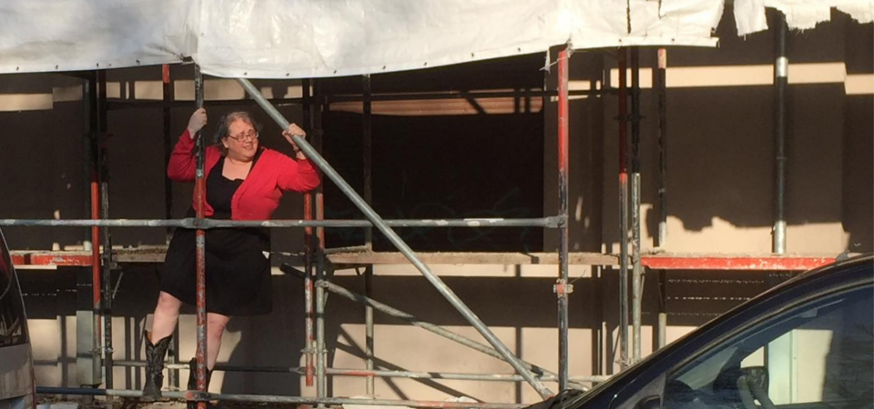 A white woman wearing a short black dress, coral cardigan sweater, black cowboy boots, and glasses is climbing up some scaffolding in front of a building. She is looking out to her left and smiling slightly, or maybe she is squinting in the afternoon soon. The edge of a white tattered tarp flaps behind her.